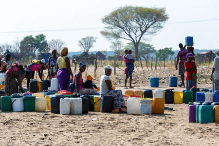 NAMIBIA, KAVANGO, OCTOBER 15: Unidentified Namibian woman with child near public tank with drinking water.Kavango region. October 15, 2014, Namibia