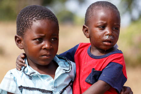 diversity of the region: NAMIBIA, KAVANGO, OCTOBER 15: Unidentified Namibian boy carries his small brother in her arms. Kavango region near Rundu. October 15, 2014, Namibia