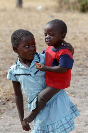 diversity of the region: NAMIBIA, KAVANGO, OCTOBER 15: Unidentified Namibian girl carries her small brother in her arms. Kavango region near Rundu. October 15, 2014, Namibia