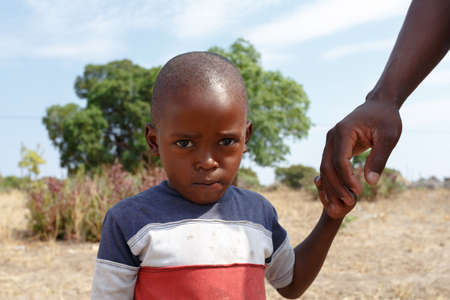 diversity of the region: NAMIBIA, KAVANGO, OCTOBER 15: An unidentified namibiann boy with father near town Rundu in Kavango region, with the highest poverty level in Namibia. October 15, 2014, Namibia