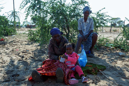diversity of the region: NAMIBIA, KAVANGO, OCTOBER 15: Unidentified Namibian woman and baby in sits in shadow from tree. Kavango is region, with the highest poverty level in Namibia. October 15, 2014, Namibia