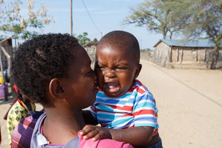 diversity of the region: NAMIBIA, KAVANGO, OCTOBER 15: Unidentified Namibian mother carries her baby in her arms.. Kavango region near Rundu. October 15, 2014, Namibia Editorial