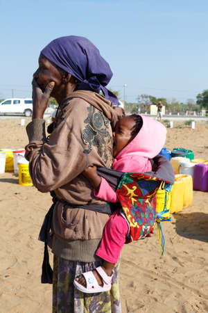 diversity of the region: NAMIBIA, KAVANGO, OCTOBER 15: An unidentified small namibian child on the back of his mother near town Rundu in Kavango region, with the highest poverty level in Namibia. October 15, 2014, Namibia