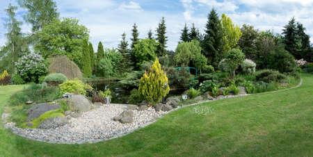 Beautiful spring garden design, with conifer trees, green grass and pond Standard-Bild