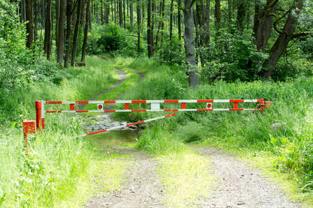 barrier gate: barrier gate on rural path with forest background usage Stock Photo