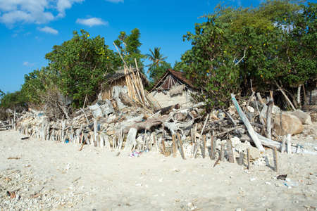 deprivation: traditional indonesian poor house - shack on beach, Nusa Penida Island, Toyapakeh. Bali. Stock Photo