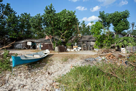 destitution: traditional indonesian poor house - cabin with boat on beach, Nusa Penida Island, Toyapakeh, Bali
