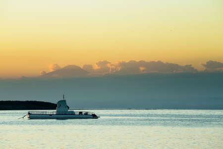 nusa: Idylic Bali sea, Nusa Penida Island, Toyapakeh, Indonesia -boat with silhouette of Bali at evening with dramatic sky