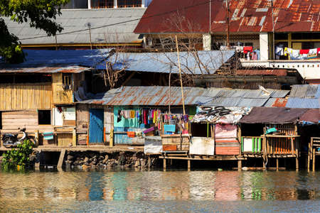 beggary: poor houses with sheet tin by the river, Kota Manado, North Sulawesi, Indonesia