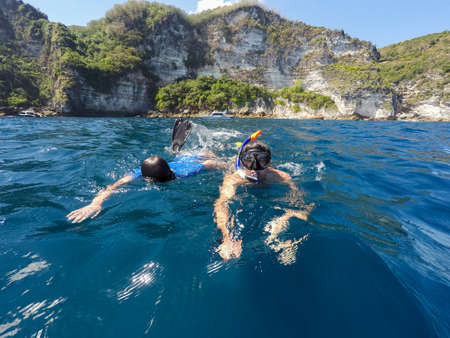 nusa: young boy snorkeling with father in a tropical sea in Nusa penida, Indonesia, Bali Stock Photo