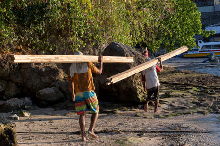 nusa: BALI, NUSA PENIDA ISLAND, INDONESIA - JULY 27.2015: Men transports cargo from ship to the shipyard in the hands. There is no other possibility to transport. Nusa Penida July 27. 2015 Indonesia