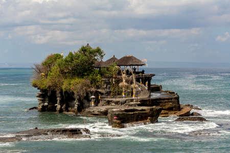 青い空と波とバリ島インドネシアの海で有名なタナロット寺院 写真素材
