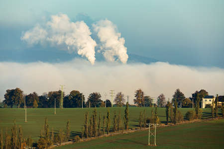 ecologic: non ecologic smoking chimneys in from factory hidden in morning mist over rural landscape Stock Photo