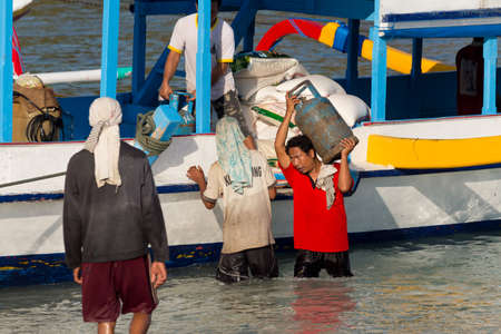 nusa: BALI, NUSA PENIDA ISLAND, INDONESIA - JULY 29.2015: Men transports cargo from ship in the hands. There is no other possibility to transport. Nusa Penida July 29. 2015 Indonesia Editorial