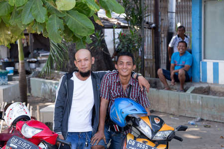 shantytown: MANADO, NORTH SULAWESI, INDONESIA - AUGUST 5, 2015: Young happy muslim teenagers with his motorbikes on August 5, 2015 in Manado, North Sulawesi, Indonesia