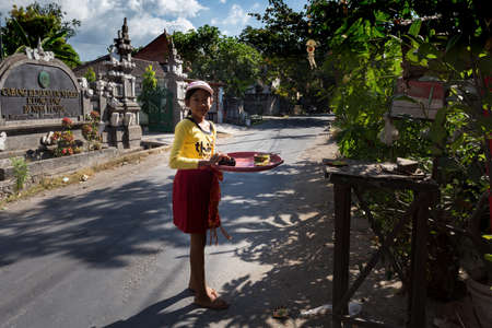 nusa: BALI, NUSA PENIDA ISLAND, INDONESIA - JULY 28, 2015: Balinese girl with offerings in front of home temple on July 27, 2015 in Nusa Penida, Indonesia