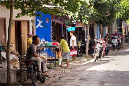penury: PENIDA ISLAND, INDONESIA - JUNE 29.2015: Hindu man resting on motorbike at street market, village Toyapakeh, Nusa Penida, Bali June 29. 2015 Indonesia