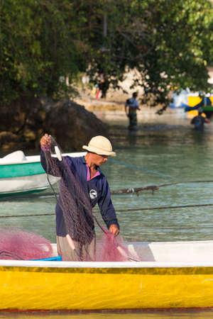 penury: PENIDA ISLAND, INDONESIA - JUNE 29.2015: Hindu fisherman men preparing net for fishing, village Toyapakeh, Nusa Penida, Bali June 29. 2015 Indonesia