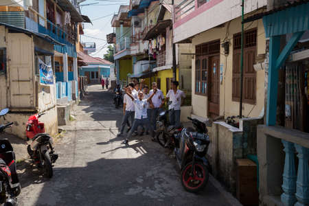 shantytown: MANADO, NORTH SULAWESI, INDONESIA - AUGUST 5, 2015:  Group of young happy muslim students in white uniform on August 5, 2015 in Manado, North Sulawesi, Indonesia