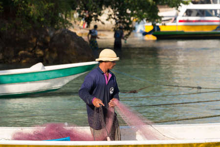 squalor: PENIDA ISLAND, INDONESIA - JUNE 29.2015: Hindu fisherman men preparing net for fishing, village Toyapakeh, Nusa Penida, Bali June 29. 2015 Indonesia