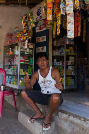 shantytown: MANADO, NORTH SULAWESI, INDONESIA - AUGUST 5, 2015: Indonesian man in front of his store in Manado shantytown on August 5, 2015 in Manado, North Sulawesi, Indonesia