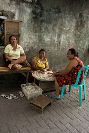 shantytown: MANADO, NORTH SULAWESI, INDONESIA - AUGUST 5, 2015: Indonesian woman peel garlic in Manado shantytown on August 5, 2015 in Manado, North Sulawesi, Indonesia Editorial