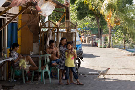 shantytown: MANADO, NORTH SULAWESI, INDONESIA - AUGUST 5, 2015: Indonesian girls with family in Manado shantytown on August 5, 2015 in Manado, North Sulawesi, Indonesia Editorial