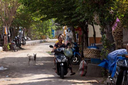 penury: PENIDA ISLAND, INDONESIA - JUNE 29.2015: woman Hindu drive motorbike on empty street market, village Toyapakeh, Nusa Penida, Bali June 29. 2015 Indonesia