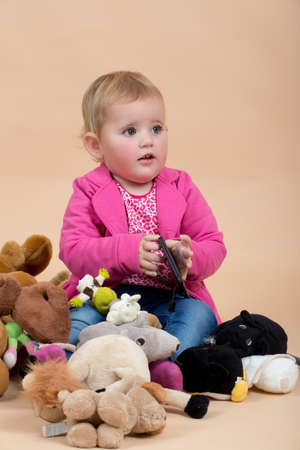 plushy: portrait of young cute baby on beige background with plushy toys Stock Photo