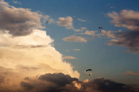 paradglider: silhouettes of unidentified skydivers parachutist on blue sky on sunset