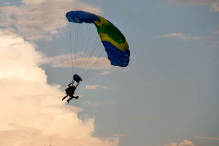 parapendio: silhouettes of unidentified skydivers parachutist on blue sky on sunset