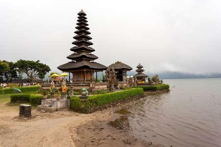 templo: El más famoso templo del agua pura Ulun Dana en un lago Beratan. Bali, tarde soleada, con niebla