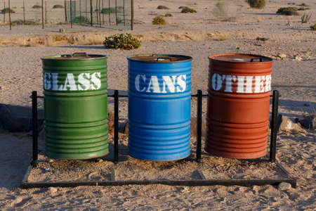 mirabilis: Different Colored Bins For Collection Of Recycle Materials near Svakopmund desert, place with biggest desert flower welvitchia mirabilis in Namibia Stock Photo