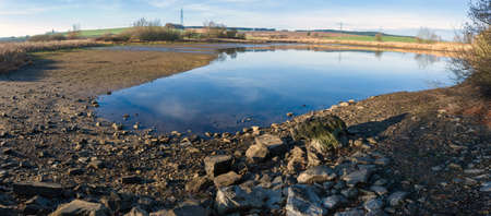 drained: drained pond in winter against blue sky, rural scene, landscape