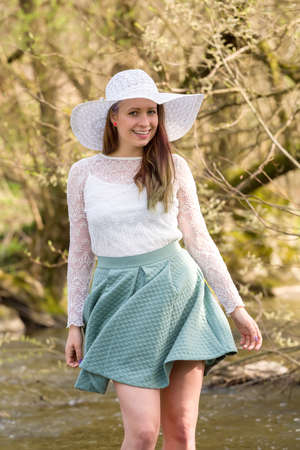 frock: Cheerful fashionable woman in stylish hat and frock posing outdoor in creek. Happy brunette girl with long hair in warm spring day
