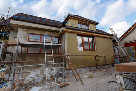 renovate old building facade: Construction or repair of the rural house, fixing facade, insulation and using color for new look