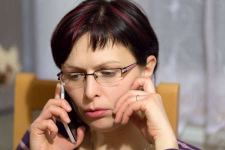 median age: beautiful middle age tired woman without makeup call by phone and getting bad news Stock Photo