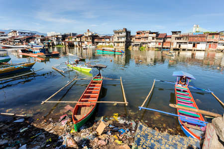 beggary: poor houses with sheet tin by the river with boats on the river,Kota Manado, North Sulawesi, Indonesia