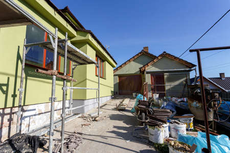 renovate old building facade: Construction or repair of the rural house, fixing facade, insulation and using color