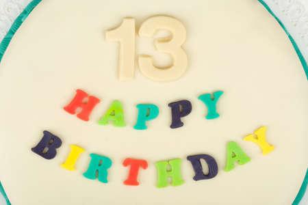 thirteen: birthday cake with text happy birthday for thirteen anniversary on white