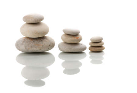 Pile of balancing pebble stones, like ZEN stone, isolated on white background, spa tranquil scene concept with reflection