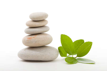 white stones: Pile of balancing pebble stones and green leaf, like ZEN stone, isolated on white background, spa tranquil scene concept with reflection