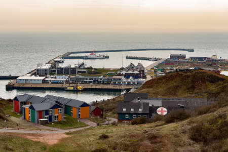 euro area: harbor Island Helgoland, Germany, nordic style houses with boat and blue sky, view from hill to north sea