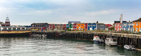 euro area: panorama of colored Crab fisher hutches at harbor Island Helgoland, Germany, nordic style houses with boat and blue sky