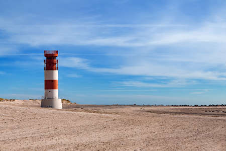 navigational light: lighthouse at heligoland dune island with blue sky, no people, on beach with harbour seal on right side Stock Photo