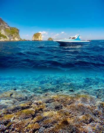 waterline: Underwater and surface split view in the tropics paradise with yacht, fish and coral reef, above waterline, beautiful view on tropical island. Nusa Penida bali, Indonesia. Stock Photo