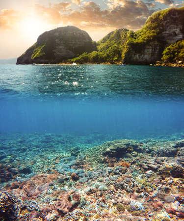 Vue sous-marine et de surface fendue sous les tropiques paradis avec le bateau, les poissons et les récifs de corail, au-dessus la ligne de flottaison, belle vue sur l'île tropicale. Nusa Penida bali, Indonésie.