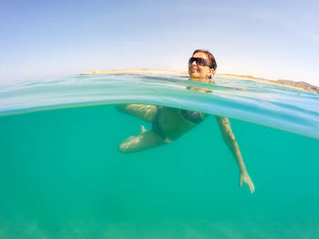 tetona: Mujer atractiva tetona edad media bastante con bikini, traje de ba�o, nadar en el Mar Rojo en Egipto. concepto de vacaciones de vacaciones. cielo azul con nubes blancas y aguas color turquesa. La mujer es feliz con una sonrisa. Foto de archivo