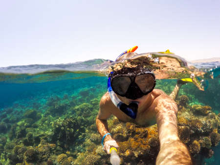 Underwater and surface split view in the tropics paradise with snorkeling man, fish and coral reef, under and above waterline, beautiful view on tropical sea. Safaga, Egypt. Holiday snorkeling vacation concept Banco de Imagens