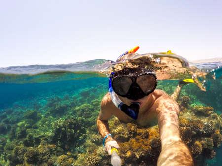 Vue sous-marine et de surface fendue sous les tropiques paradis avec snorkeling l'homme, les poissons et les récifs de corail, sous et au-dessus la ligne de flottaison, belle vue sur la mer tropicale. Safaga, Egypte. snorkeling vacances vacances notion